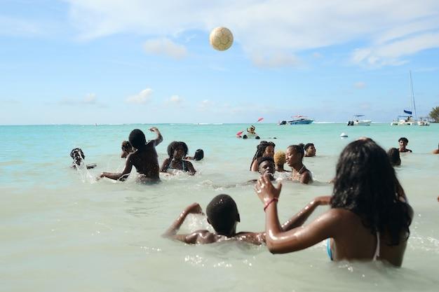 8 grudnia 2019 wyspa mauritius, miejscowi pływają w oceanie indyjskim i bawią się piłką.