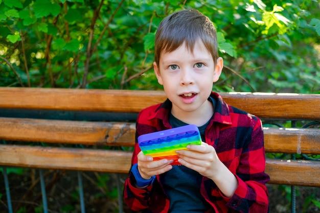 8-letni chłopiec bawi się z popitem w parku. szczęśliwe dziecko z zabawką. dziecko nosi jasne letnie ubrania na co dzień. wielobarwny pop to zbliżenie. plastikowa zabawka antystresowa.