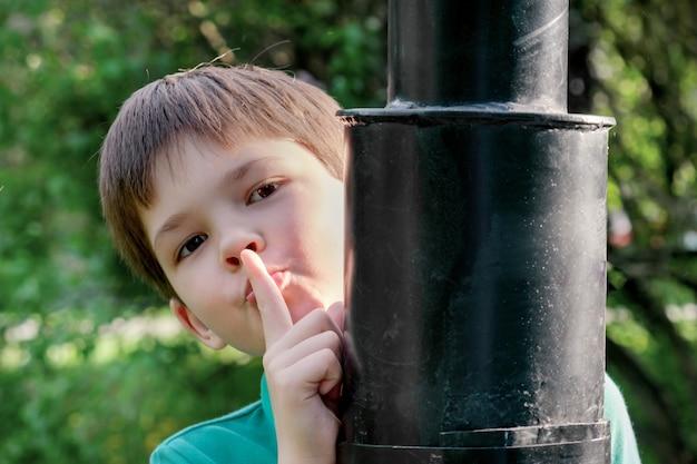 8-letni chłopiec o ciemnych włosach stoi za metalową latarnią i cicho pokazuje gest. koncepcja komunikacji z dziećmi, dochowanie tajemnic, lęk przed komunikowaniem się dzieci z dorosłymi.