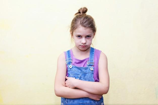 8-letnia dziewczynka z niezadowoloną miną, krzyżująca ręce na piersi