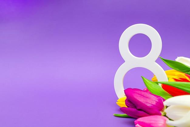 8 marca, międzynarodowy dzień kobiet. tulipany na fioletowym tle, miejsce na tekst. nadaje się na reklamę, pocztówki, gratulacje.
