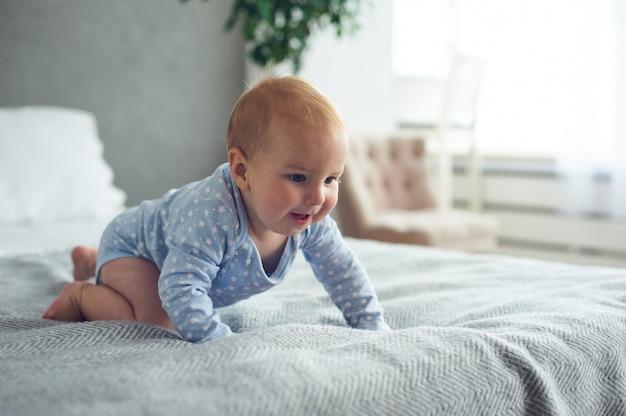8-miesięczny szczęśliwy chłopczyk czołgający się na łóżku w domu