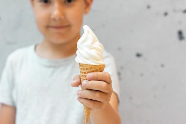 8 roczniaka chłopiec trzyma out waniliowego lody w gofra rożku na popielatym tle, selekcyjna ostrość
