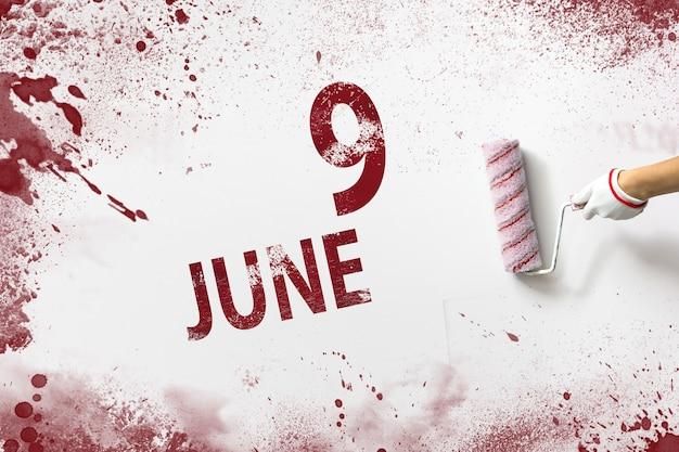9 czerwca. dzień 9 miesiąca, data kalendarzowa. ręka trzyma wałek z czerwoną farbą i pisze datę w kalendarzu na białym tle. miesiąc letni, koncepcja dnia roku.