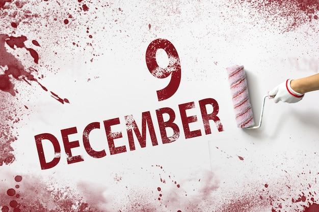 9 grudnia. dzień 9 miesiąca, data kalendarzowa. ręka trzyma wałek z czerwoną farbą i pisze datę w kalendarzu na białym tle. miesiąc zimowy, koncepcja dnia roku.