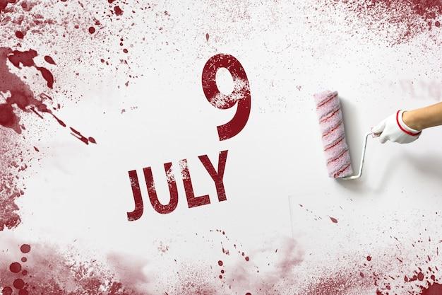 9 lipca. dzień 9 miesiąca, data kalendarzowa. ręka trzyma wałek z czerwoną farbą i pisze datę w kalendarzu na białym tle. miesiąc letni, koncepcja dnia roku.