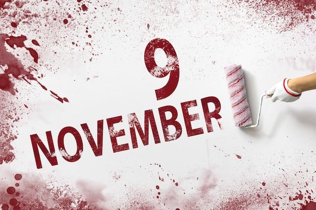 9 listopada. dzień 9 miesiąca, data kalendarzowa. ręka trzyma wałek z czerwoną farbą i pisze datę w kalendarzu na białym tle. jesienny miesiąc, koncepcja dnia roku.