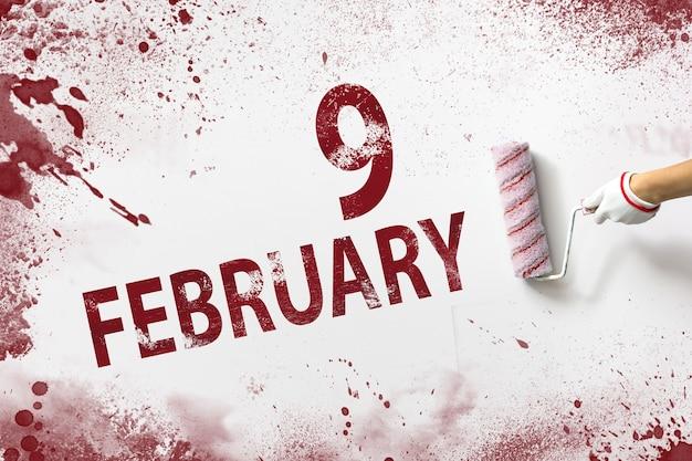 9 lutego. dzień 9 miesiąca, data kalendarzowa. ręka trzyma wałek z czerwoną farbą i pisze datę w kalendarzu na białym tle. miesiąc zimowy, koncepcja dnia roku.