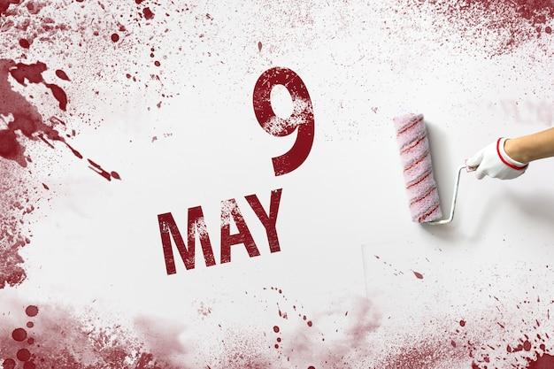 9 maja. dzień 9 miesiąca, data kalendarzowa. ręka trzyma wałek z czerwoną farbą i pisze datę w kalendarzu na białym tle. miesiąc wiosny, koncepcja dnia roku.