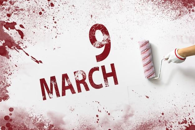 9 marca. dzień 9 miesiąca, data kalendarzowa. ręka trzyma wałek z czerwoną farbą i pisze datę w kalendarzu na białym tle. miesiąc wiosny, koncepcja dnia roku.