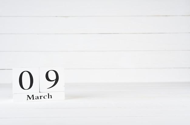 9 marca, dzień 9 miesiąca, urodziny, rocznica, drewniany kalendarz blokowy na białym drewnianym tle z kopią miejsca na tekst.