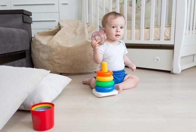 9-miesięczny chłopiec bawi się na podłodze z zabawkową wieżą
