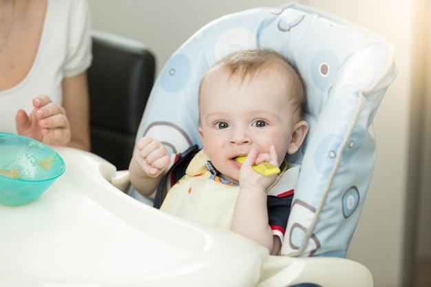 9-miesięczny chłopiec z łyżką siedzi w krzesełku
