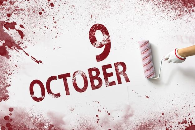 9 października. dzień 9 miesiąca, data kalendarzowa. ręka trzyma wałek z czerwoną farbą i pisze datę w kalendarzu na białym tle. jesienny miesiąc, koncepcja dnia roku.