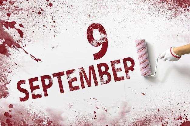 9 września. dzień 9 miesiąca, data kalendarzowa. ręka trzyma wałek z czerwoną farbą i pisze datę w kalendarzu na białym tle. jesienny miesiąc, koncepcja dnia roku.