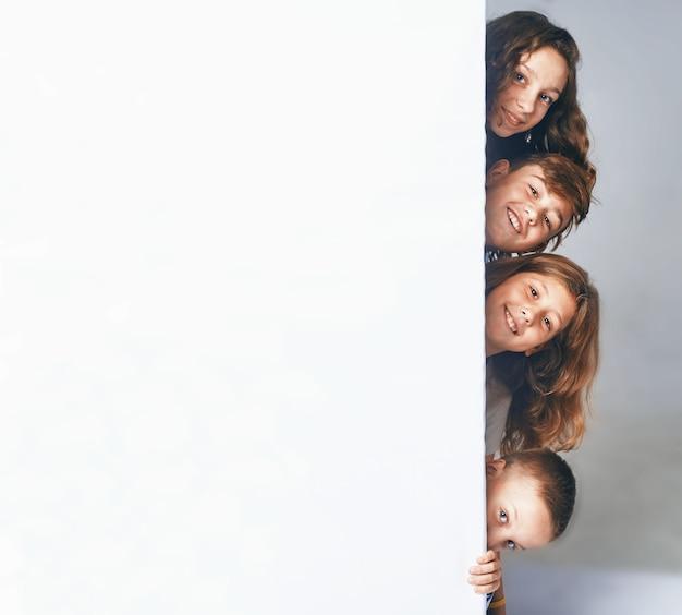 A czwórka dzieci trzymających duży billboard, pojawia się z boku billboardu