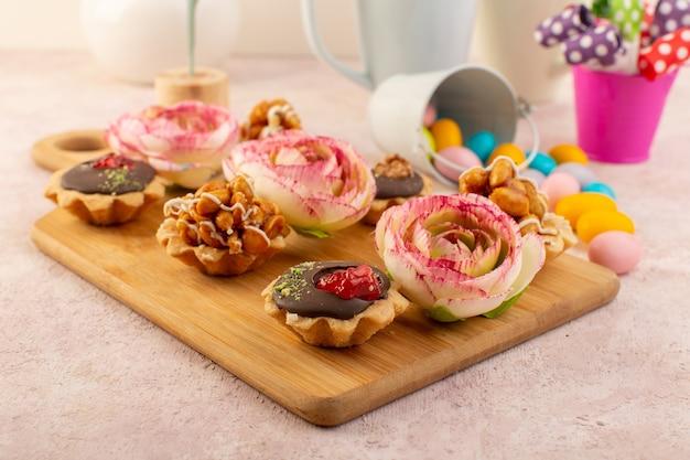 A fornt view little chooclate cakes z kwiatkiem i kolorowymi cukierkami
