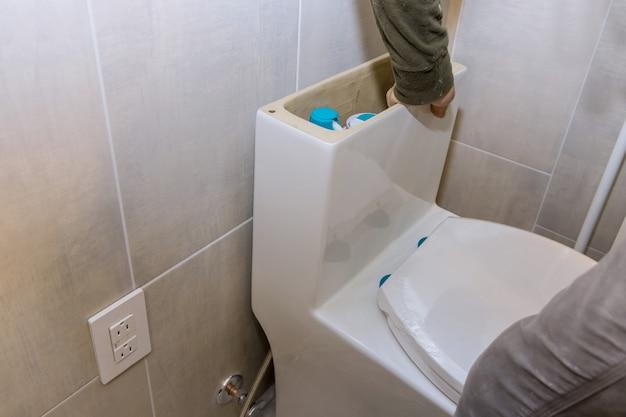 A instalacja nowej łazienki do spłukiwania hydraulika z instalacją nowej białej miski wc