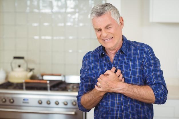starszy mężczyzna cierpiący na zawał serca w kuchni