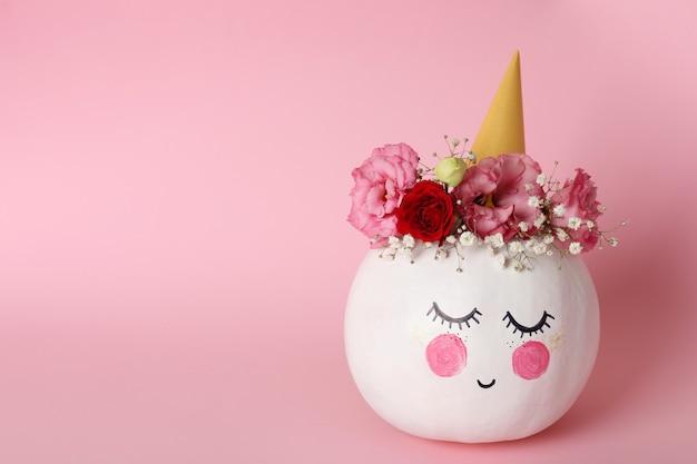à ¡ute dynia z halloweenowym makijażem na różowym tle