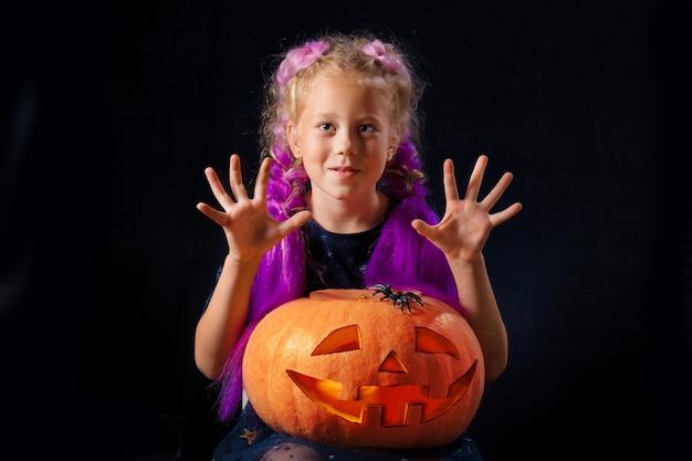 A w kostiumie karnawałowym bawi się pomarańczową dynią i pająkiem.