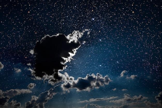 A wynurza nocne niebo z gwiazdami, księżycem i chmurami.