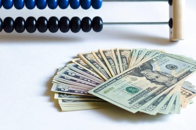 Abakusa i dolarów fan na bielu stole