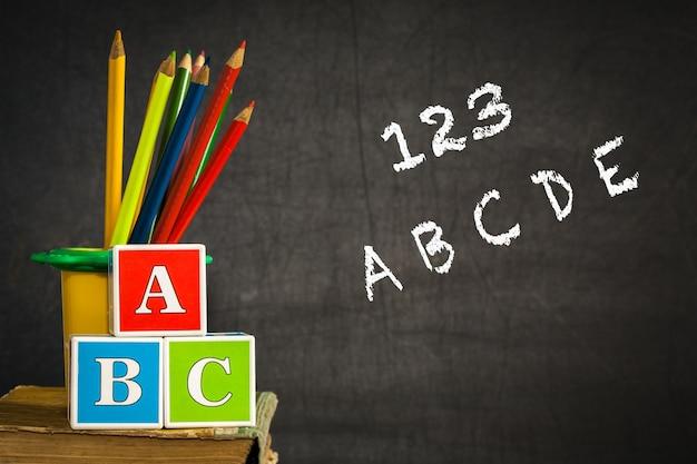 Abc i wielokolorowe ołówki na starych książkach w klasie przed tablicą. koncepcja szkoły