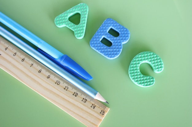 Abc - litery alfabetu angielskiego na zielonym tle obok pióra, ołówka i linijki.