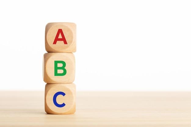 Abc litery alfabetu na drewnianych klockach ułożone na drewnianym stole.