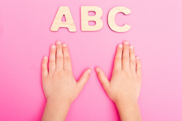 Abc litery w rękach dziecka na różowym tle