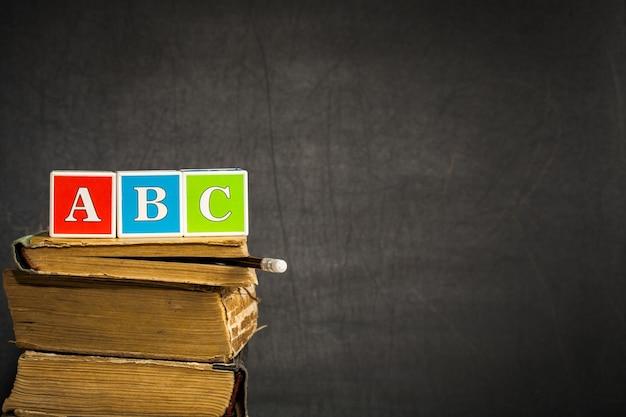 Abc na starych książkach przeciw tablicy z miejscem na tekst. koncepcja szkoły