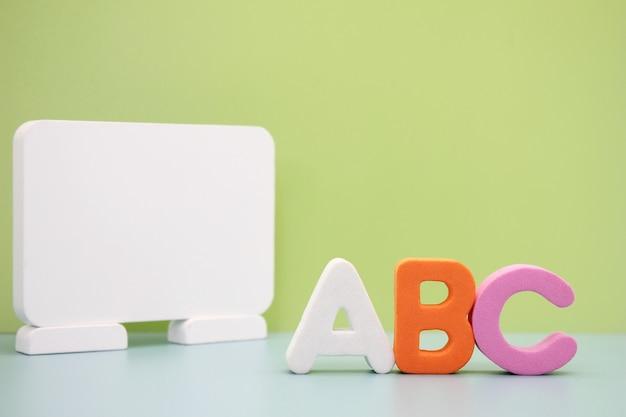 Abc - pierwsze litery alfabetu angielskiego w pobliżu białej tablicy. koncepcja edukacji.
