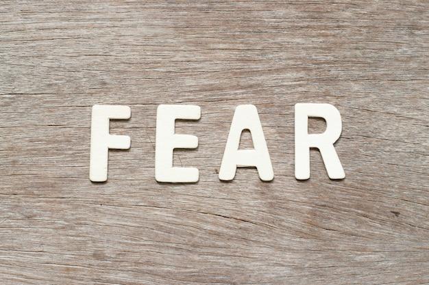 Abecadło list w słowo strachu na drewnianym tle