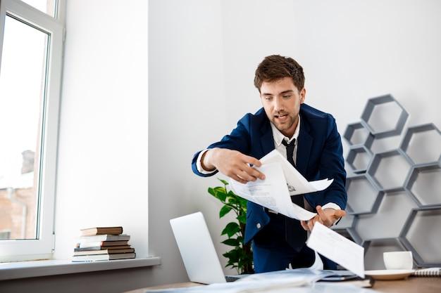 Absentminded młody biznesmen szperanie w papierach, tło pakietu office.