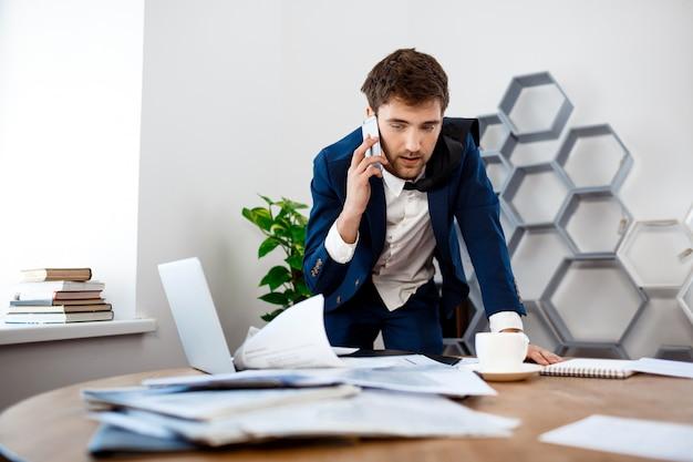 Absentminded młody biznesmena mówienie na telefonie, biurowy tło.