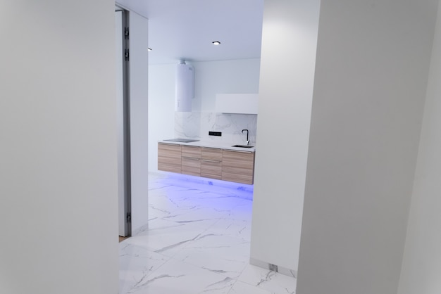 Absolutnie oszałamiające wnętrze kuchni w jasnych kolorach z niebieskim oświetleniem blatów z drewna i marmuru