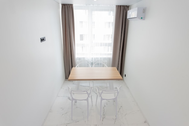 Absolutnie oszałamiające wnętrze kuchni w jasnych kolorach ze stołem jadalnym przy krzesłach przy oknie