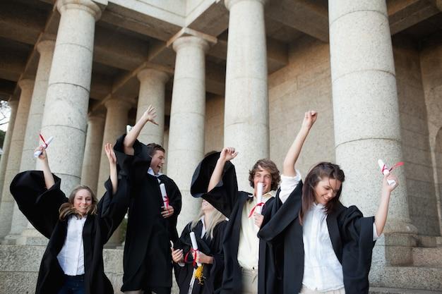 Absolwenci tańczący w togach