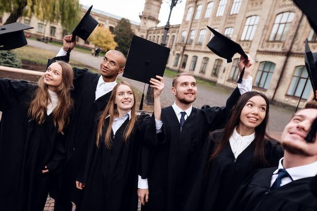 Absolwenci uniwersytetu rzucają czapkami.