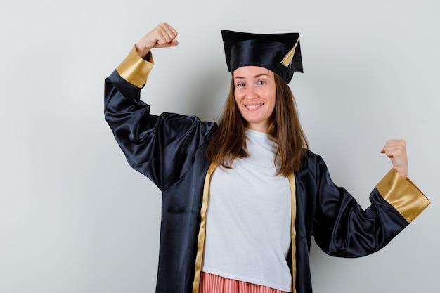 Absolwent kobieta pokazując gest zwycięzcy w ubranie, mundur i wyglądający wesoło. przedni widok.