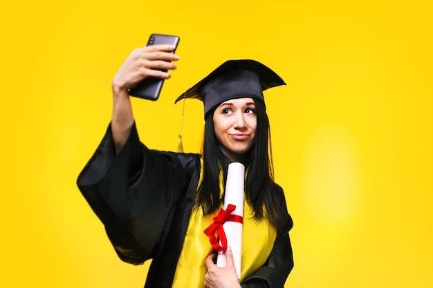 Absolwent kobieta robi zdjęcie selfie nad żółtą przestrzenią