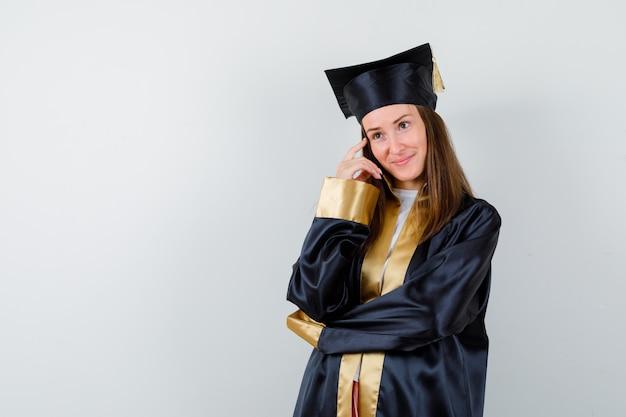 Absolwent kobieta stojąc w myśleniu poza w akademickim stroju i patrząc wesoło, widok z przodu.