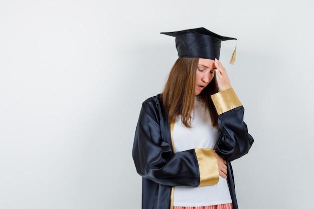 Absolwent kobieta trzyma rękę na głowie w ubranie, mundur i wygląda na zmęczonego, widok z przodu.