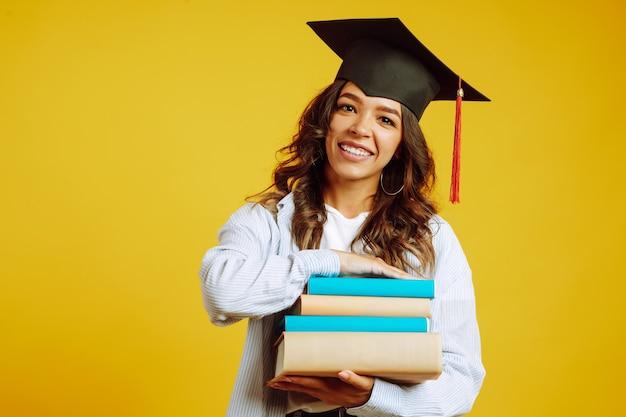 Absolwent kobieta w kapeluszu dyplomowym na głowie, z książkami na żółto.
