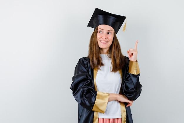 Absolwent kobieta w ubranie, mundur skierowany w górę i patrząc z nadzieją, widok z przodu.