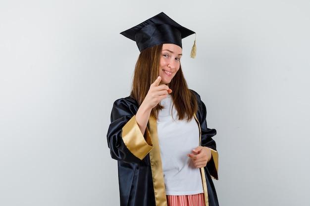 Absolwent kobieta, wskazując na aparat w ubranie, mundur i pewny siebie. przedni widok.