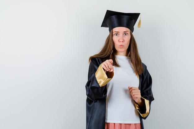Absolwent kobieta, wskazując na aparat w ubranie, mundur i wyglądający na oszołomionego. przedni widok.