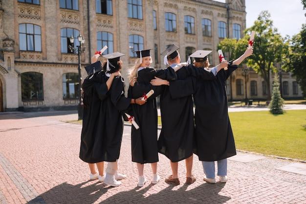 Absolwent oglądający się za siebie, podczas gdy inni stoją obok siebie i podnoszą ręce przed uniwersytetem
