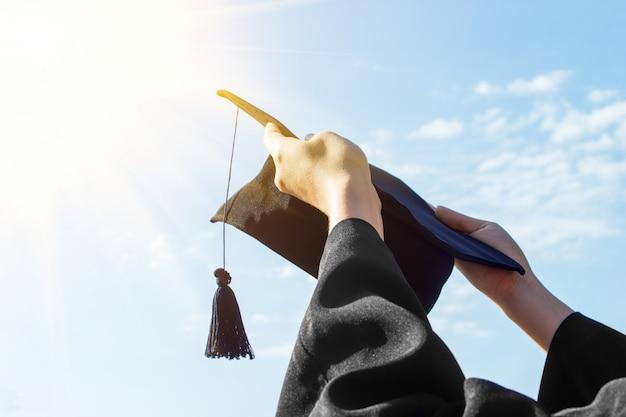 Absolwent świętuje z kapelusza w ręku w dniu rozpoczęcia